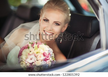 wedding: happy beautiful bride in car with bridal bouquet hairstyle and bright makeup. Blond woman in white dress at wedding day waiting for groom and posing. Concept of happiness and love. Newlywed - stock photo