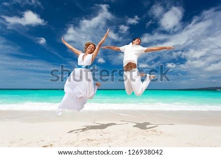 Wedding happy couple jumping on the beach - stock photo