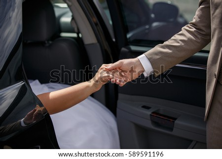 wedding help bride and groom holding hands near just married car