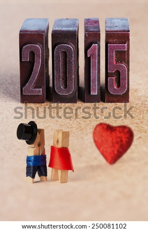 Wedding invitation. Valentines day. 2015 written with colored vintage letterpress. Groom in black hat and bride in red dress. Clothespins. (Soft focus) - stock photo