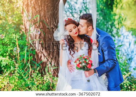 wedding, just married couple kiss in a forest by the lake