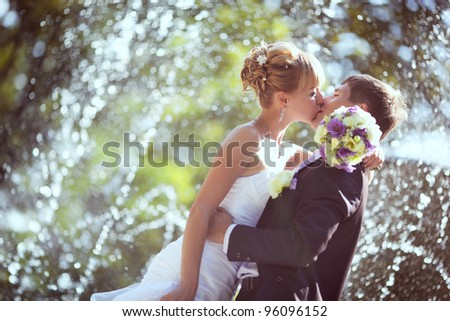 wedding kiss in the park with a fountain - stock photo