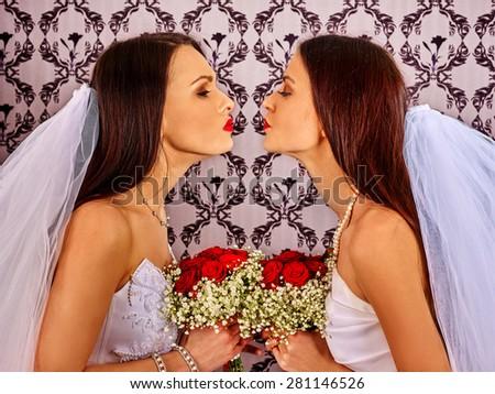 Wedding lesbians girl in bridal dress kissing. Indoor. - stock photo