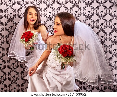 Wedding lesbians girl in bridal dress. Wallpaper in background