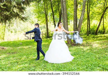 Wedding, love, relationships, marriage. Smiling bride and groom with blue smoke