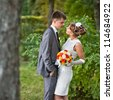 Wedding: Lovely young couple standing in a park and hug each other in theirs wedding day - Copyspace - stock photo