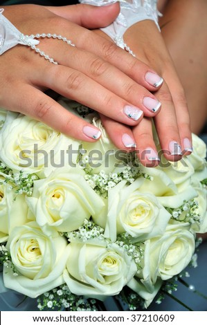 wedding manicure on hands of bride, they are laying on weddind flowers