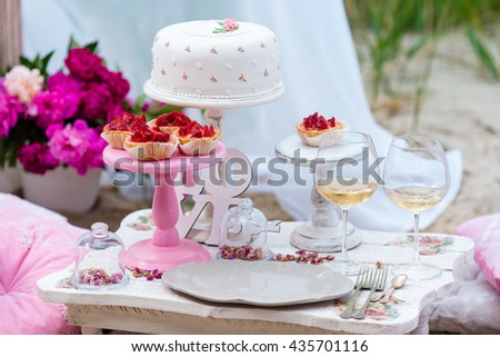 Wedding or party candy bar, decorated dessert table in pink color with cakes. Shabby chic style