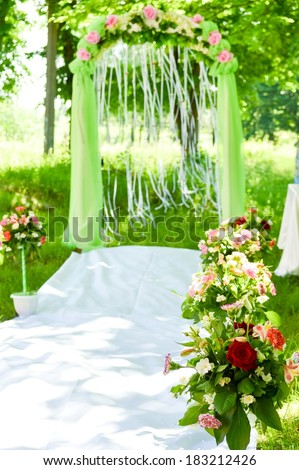 Wedding outdoor ceremony arch flower decoration on the green summer background  - stock photo