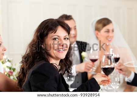 Wedding party at dinner - the bridal couple in the background - stock photo