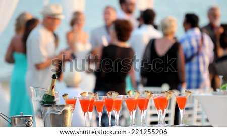 Wedding Party. Red cocktails in glasses and cold champagne ready for party people. Cold chilled champagne in ice bucket and glasses of red cocktail at outdoor wedding reception. - stock photo