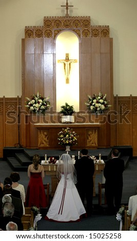 wedding party standing at altar in catholic church during wedding ceremony - stock photo