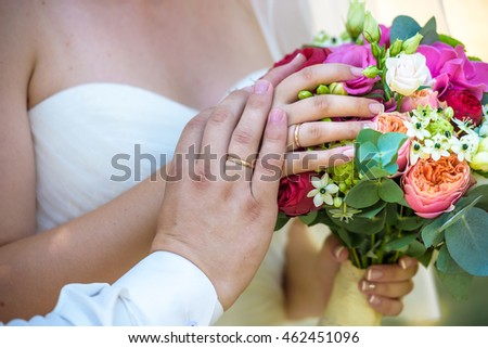 Wedding pastel bouquet closeup in front of couple - groom and bride's hands with elegant manicure. Flowers lay on the dress with swan feather decor