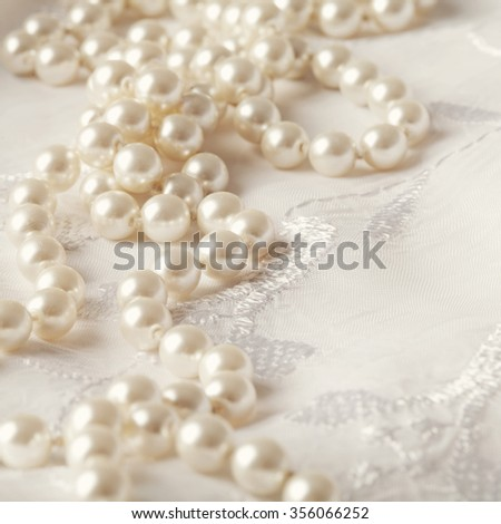 wedding pearl necklace on white floral background - stock photo