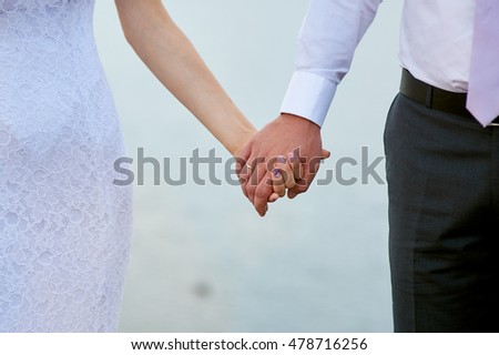 Wedding photo of bride and groom holding hands