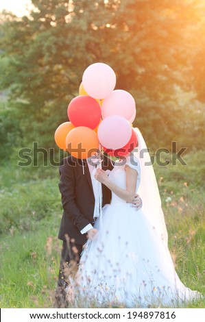 wedding photo - very beautiful couple with balloons at sunset - stock photo