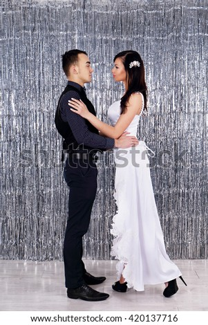 Wedding photo. Young bride and groom dancing on glittering background - stock photo
