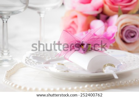 Wedding place setting with small present for guests - stock photo
