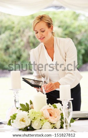 Wedding Planner Checking Table Decorations In Marquee - stock photo