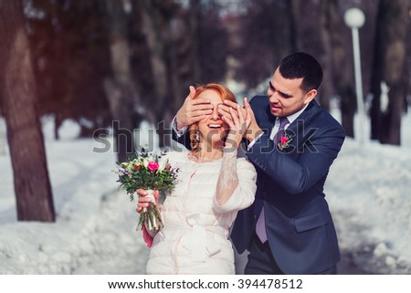 Wedding Portrait of groom shutting eyes of his bride by hands - stock photo