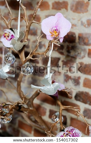 Wedding reception decorations in closeup detail showing bonsai tree with doves and flowers