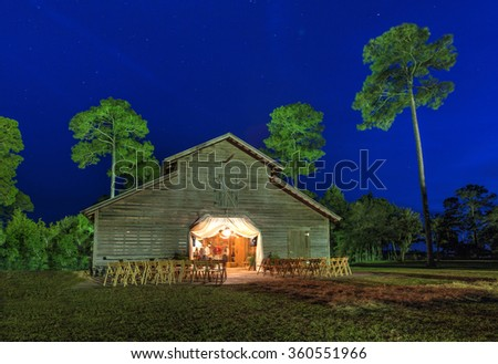 Wedding reception in lit up barn at night - stock photo