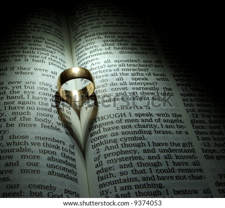 Wedding Ring and heart shaped shadow over a Bible - stock photo