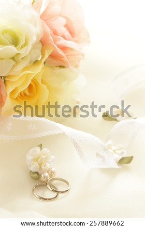 Wedding ring on fabric with artificial flower for background image - stock photo