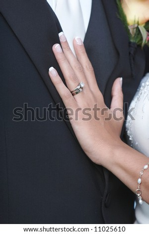 Wedding ring on hand of bride on groom - stock photo