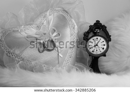 wedding ring on heart pillow, soft fabric background, black and white photo - stock photo