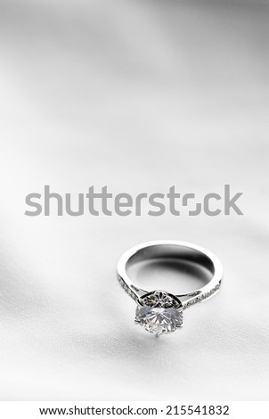 Wedding ring on white fabric background