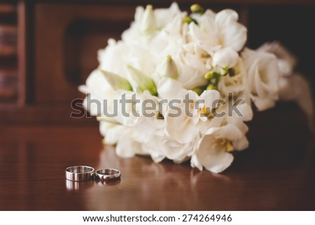 Wedding rings and bouquet - stock photo