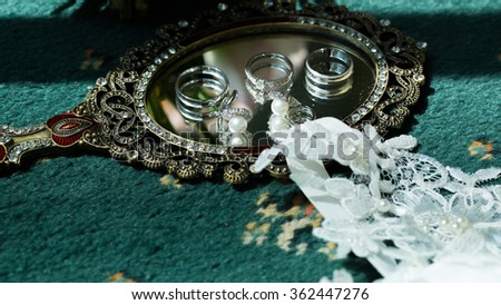 Wedding rings and earrings lying on a mirror. Wedding accessories
