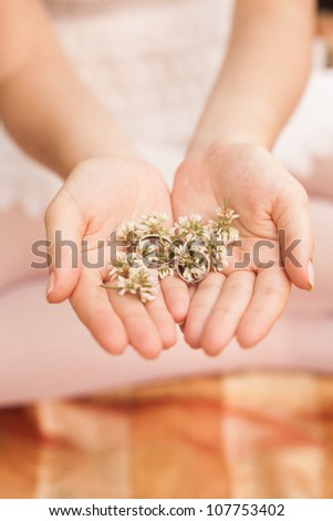 wedding rings and flowe in the hands of the bride - stock photo