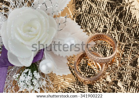 Wedding rings and flowers on a golden fabric - stock photo