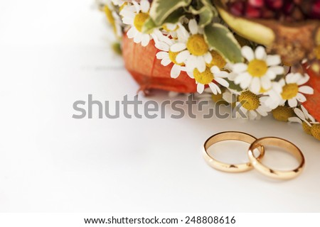wedding rings and flowers on white background - stock photo