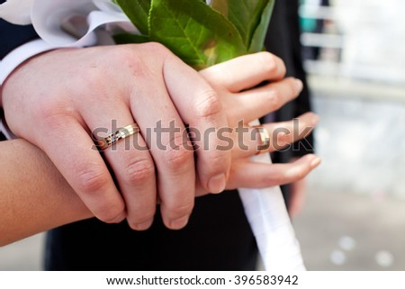 Wedding rings and hands on bridal bouquet