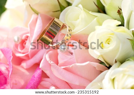 Wedding rings and pink roses bouquet - stock photo