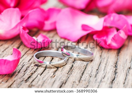 Wedding rings and pink roses petals - stock photo