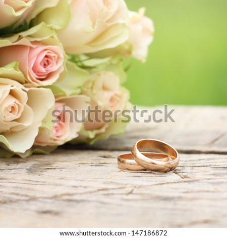 Wedding rings and roses bouquet - stock photo