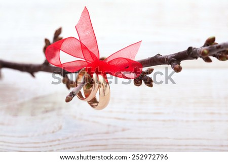 Wedding rings and wedding bouquet of red roses on wooden table. Selective focus, background is blurred, horizontally - stock photo