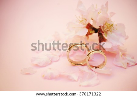 Wedding rings closeup with pink almond flowers - stock photo