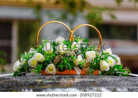 Wedding rings decorated with flowers on car after the rain - stock photo