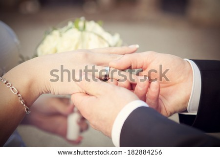 wedding rings, hand and flowers in the wedding photo - stock photo