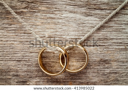 Wedding rings hanging on rope over wooden background.  - stock photo