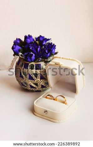 Wedding rings in a box on the flowers background. - stock photo