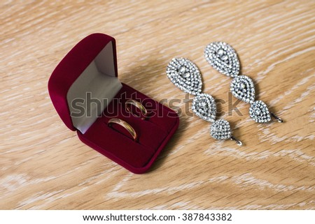 Wedding rings in a red box bride earrings and bracelet on a wooden background, preparation for the wedding  - stock photo