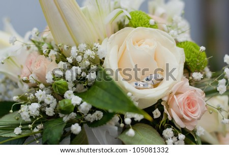 Wedding rings in bouquet - stock photo