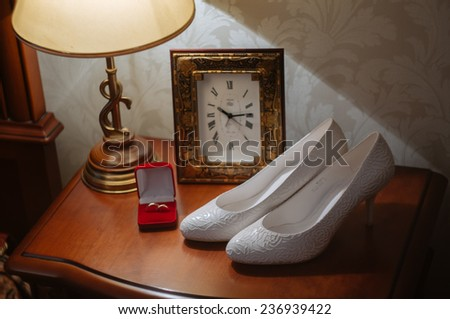 wedding rings in box on a nightstand with lamp and shoes - stock photo