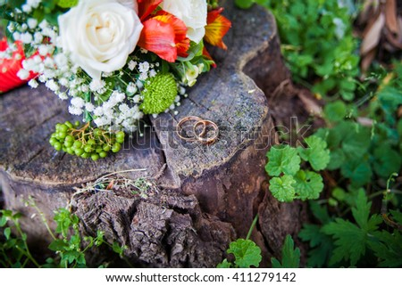 Wedding rings in gold lie with the flowers on a tree stump